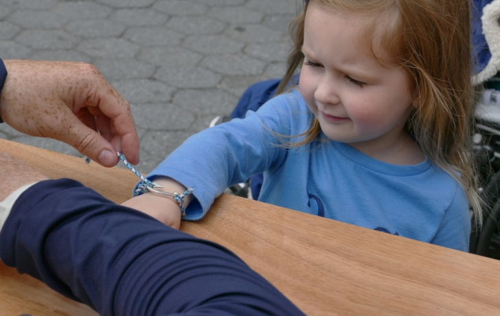 Mackenzie Brown, 3, tries on her nautically-tied bracelet. She was assisted by Jim Moore, the North Cove Marina's fleet and club manager. Photo: Carl Glassman/Tribeca Trib